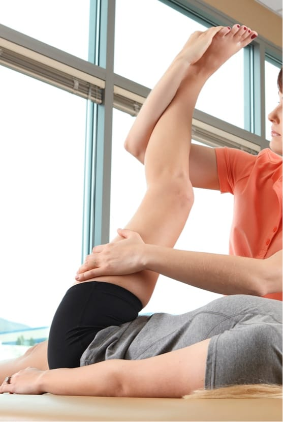 Woman having hip stretched by a professional
