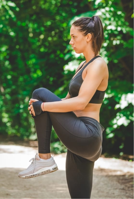 Woman stretching hamstring outside, working out