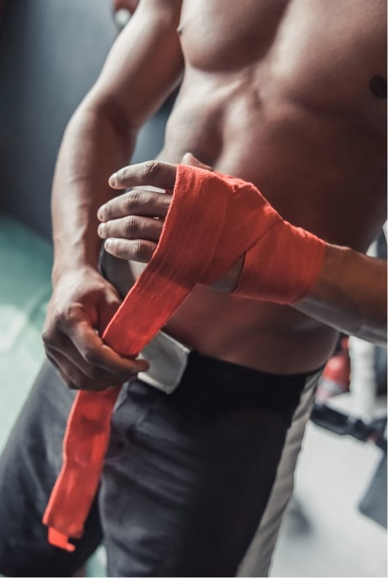Shirtless man wrapping hand at the gym