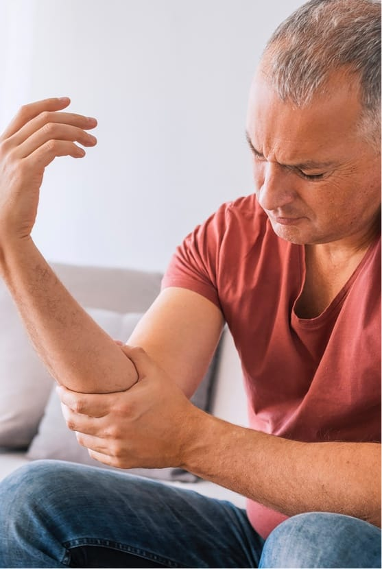 Middle-aged man grabbing elbow in discomfort