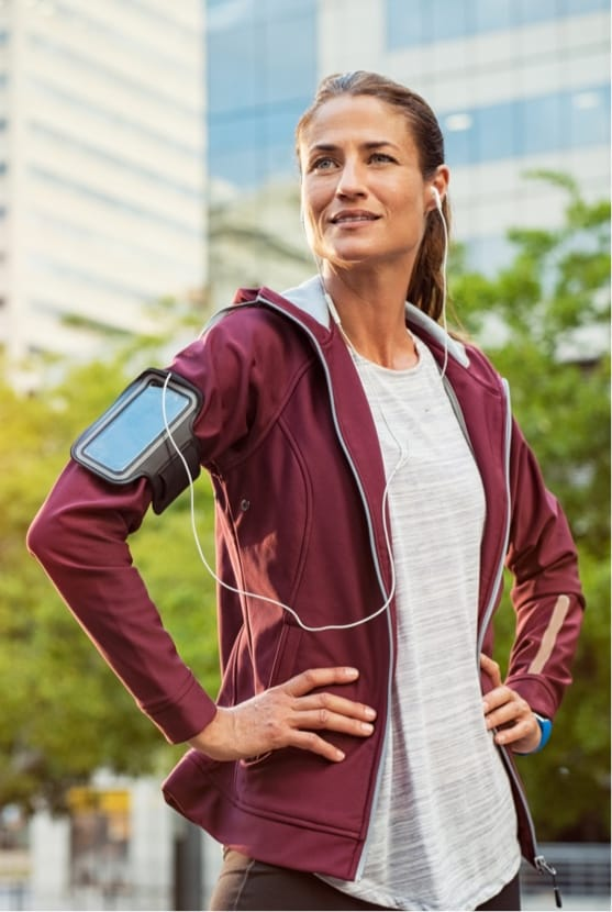Woman standing outside wearing workout clothes and headphones in