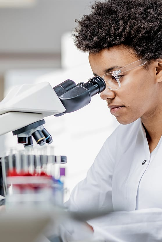 Lab technician looking into microscope lens