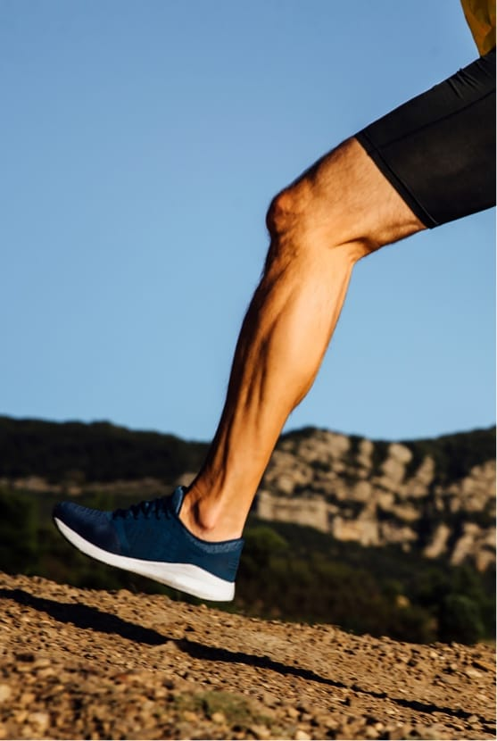 Close up of men's calf while hiking up a mountain
